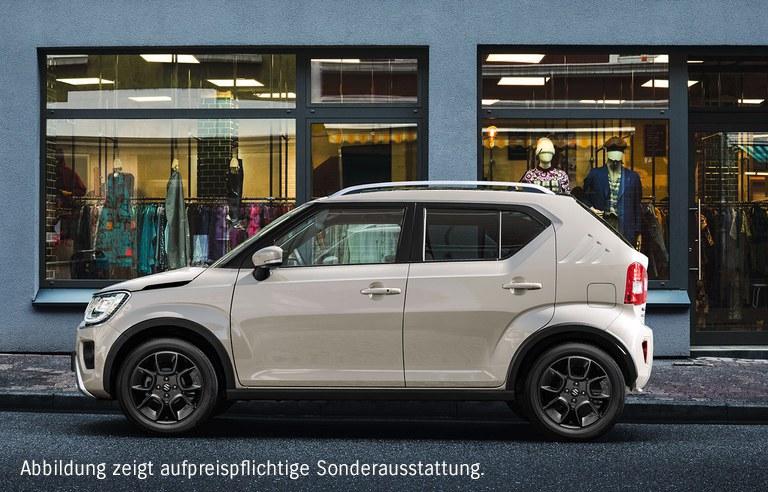 Suzuki Ignis Hybrid in Caravan Ivory Pearl Metallic parkt am Straßenrand vor einem Modegeschäft.