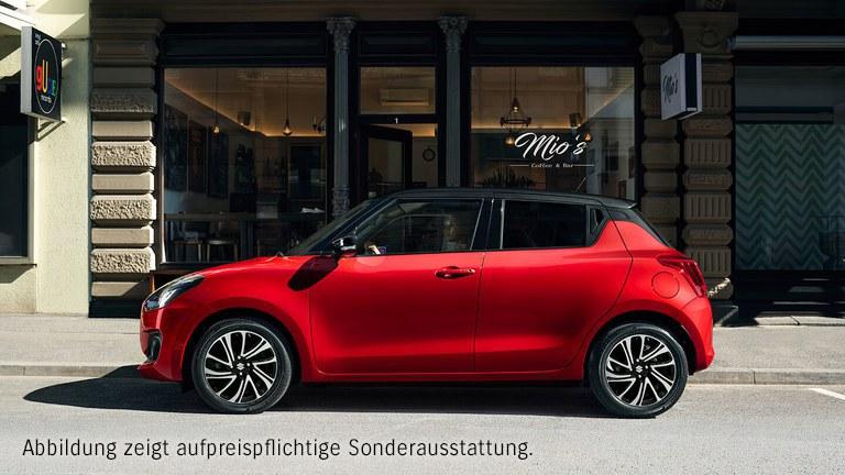 Suzuki Swift Hybrid in Red Pearl Metallic parkt vor einem Café mit dem Namen Mio's.