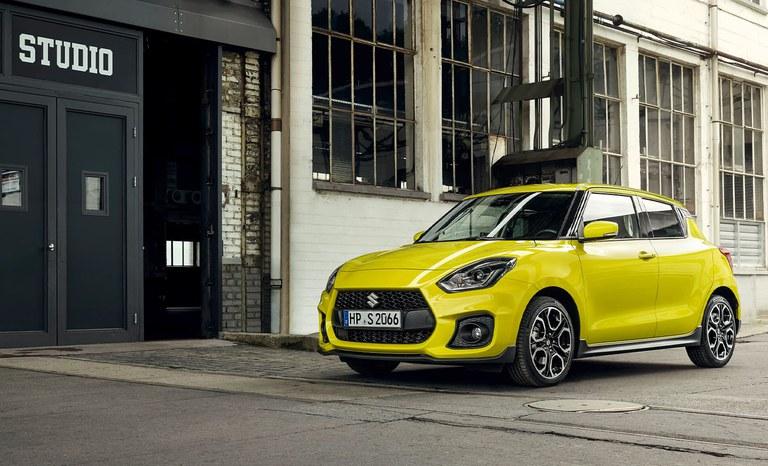 Suzuki Swift Sport Hybrid in Champion Yellow steht vor einem Studio.