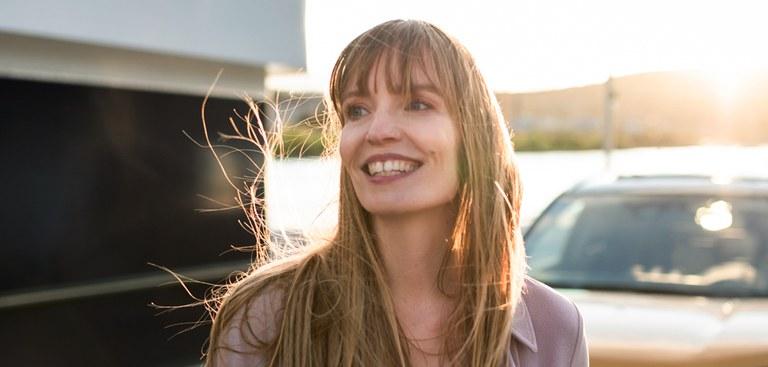 Lachende Frau mit Suzuki Modell im Hintergrund
