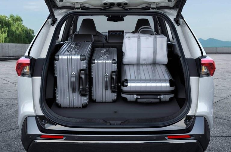 Von hinten fotografierter Suzuki Across Hybrid in White Pearl Crystal Shine Metallic mit offenem Gepäckraum