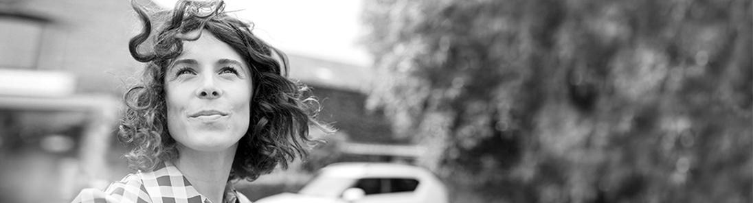 Frau mit lockigen Haaren und kariertem Oberteil schaut in die Luft.