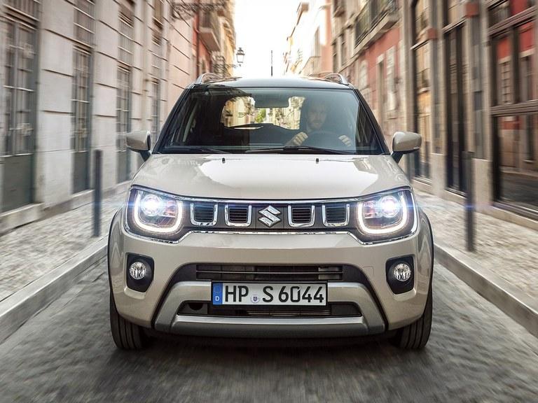 Frontansicht des Suzuki Ignis Hybrid in Caravan Ivory Perl Metallic mit eingeschaltetem Licht.