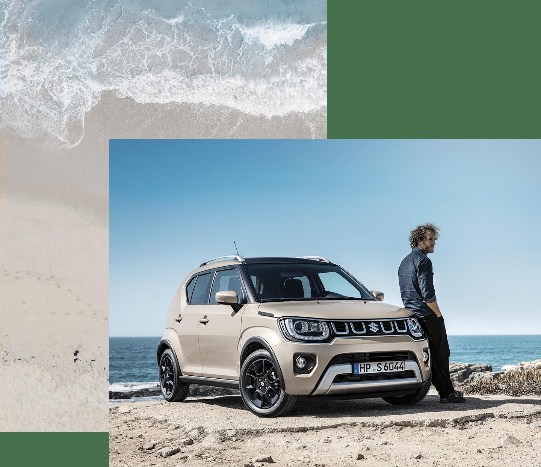 Suzuki Ignis Hybrid in Caravan Ivory Pearl Metallic an dem ein Mann lehnt, steht an einer Bucht.