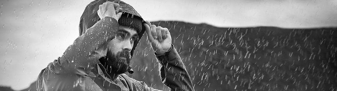 Mann mit Regenjacke steht im Regen und fasst sich an die Kapuze.
