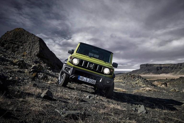 Suzuki Jimny in Kinetic Yellow in einer Berglandschaft.