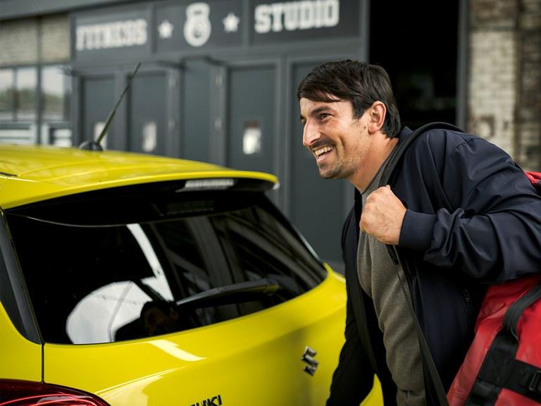 Mann mit Rucksack öffnet Kofferraum von Swift Sport