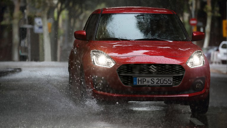 Suzuki Swift Hybrid in Burning Red Pearl Metallic im Regen.