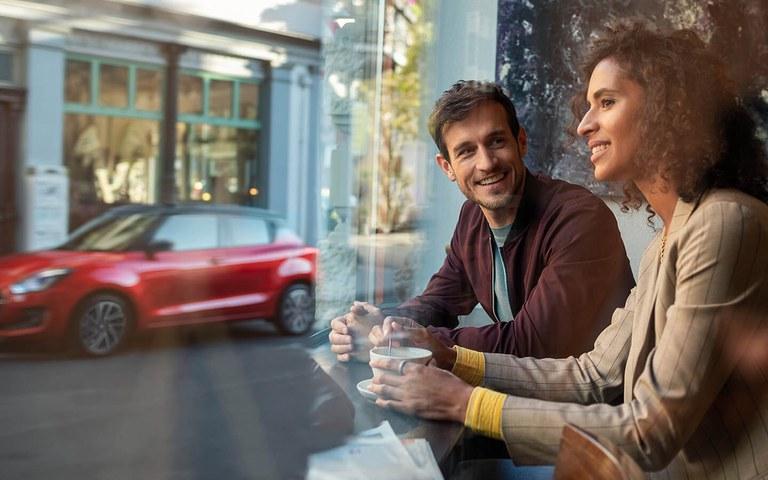 Ein Mann und eine Frau sitzen im Cafe am Fenster, im Hintergrund steht ein Suzuki Swift Hybrid in Burning Red Pearl Metallic.