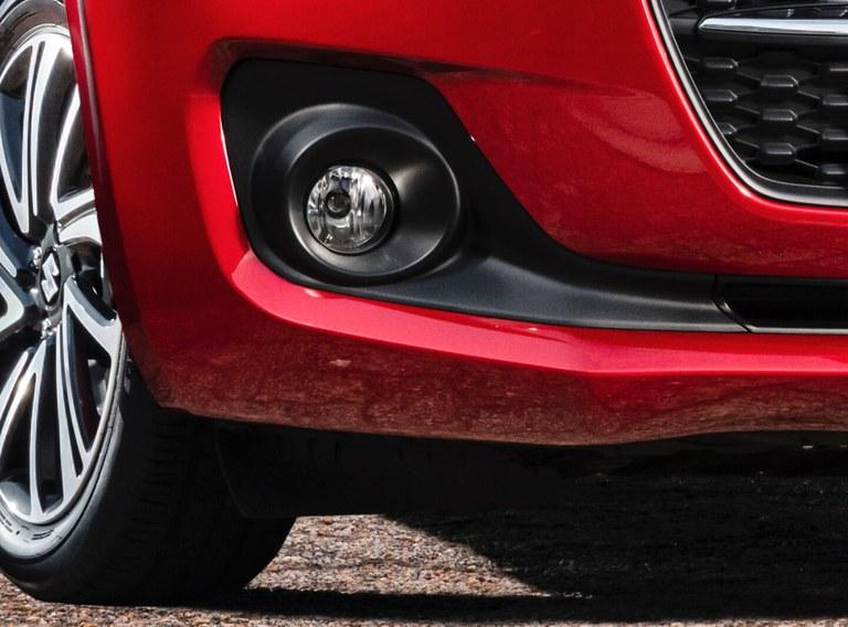 Detailaufnahme des linken Nebelscheinwerfers eines Suzuki Swift Hybrid in Burning Red Pearl Metallic.