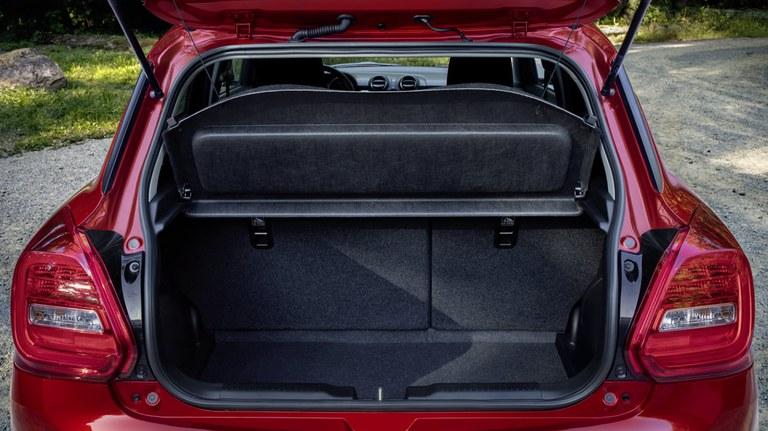 Von hinten fotografierter Suzuki Swift Hybrid in Burning Red Pearl Metallic mit offenem Gepäckraum
