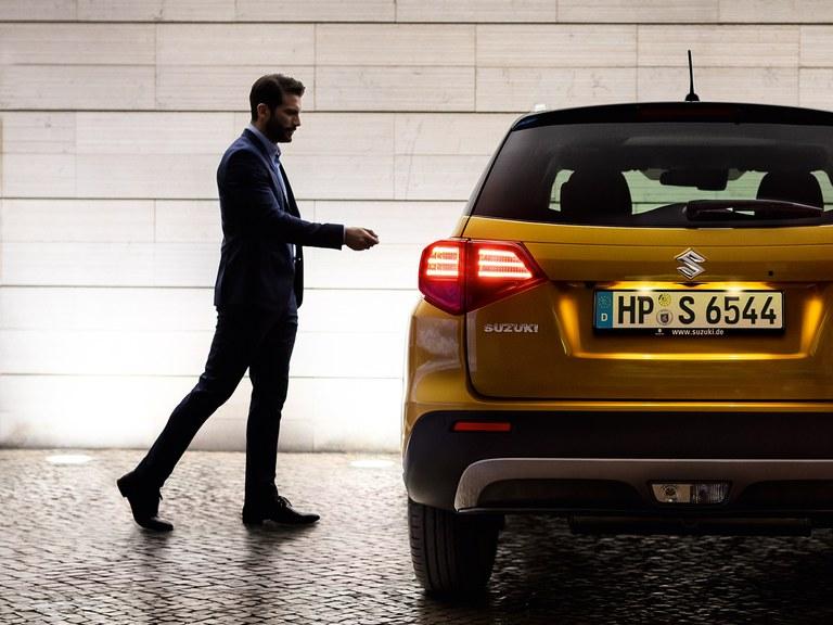 Suzuki Vitara Hybrid in Solar Yellow Pearl Metallic, Mann in dunkelblauem Anzug daneben, welcher gerade den Schlüssel bedient.