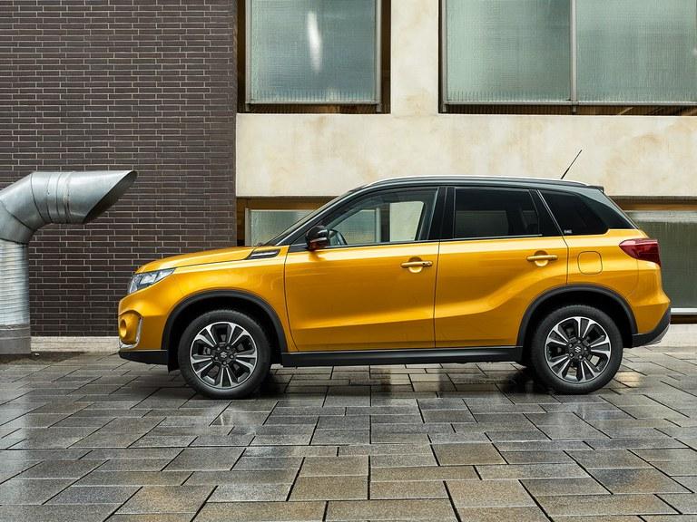 Seitlich fotografierter Suzuki Vitara Hybrid in Solar Yellow Pearl Metallic mit Privacy Glass an dne hinteren Fenstern