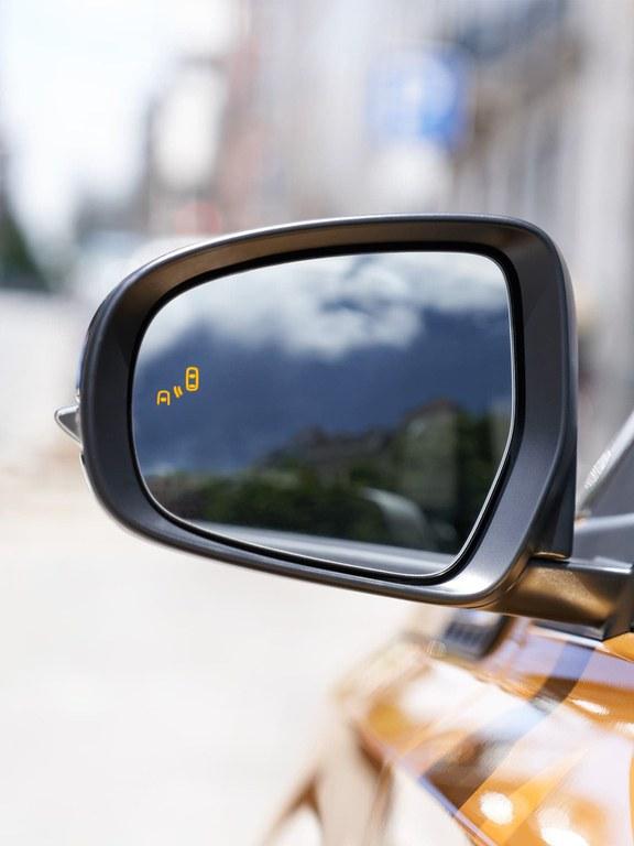 Detailaufnahme des linken Seitenspiegels eines Suzuki Vitara Hybrid in Solar Yellow Pearl Metallic.