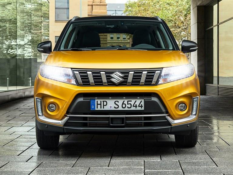 Frontansicht eines Suzuki Vitara Hybrid in Solar Yellow Pearl Metallic mit eingeschaltetem Licht.