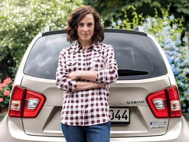 Eine Frau steht vor dem Heck eines Suzuki Ignis Hybrid in Pure White Pearl Metallic.