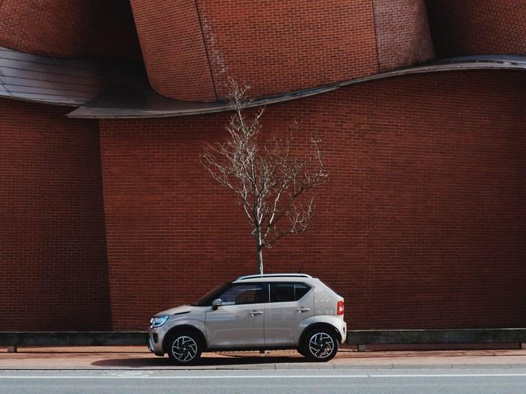 Ein Mann geht von einem Suzuki Ignis Hybrid in Pure White Pearl Metallic weg, welcher vor einem Modegeschäft geparkt ist.