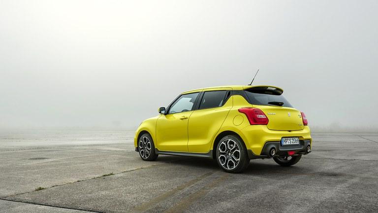 Leicht seitlich von hinten fotografierter Suzuki Swift Sport Hybrid in Champion Yellow auf einer freien Fläche.