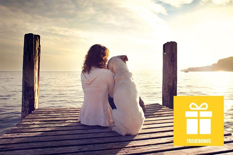 Eine Frau auf einem Steg, neben ihr ein heller Labrador. Außerdem ein Icon in Geschenkform, darunter steht Truebonus.