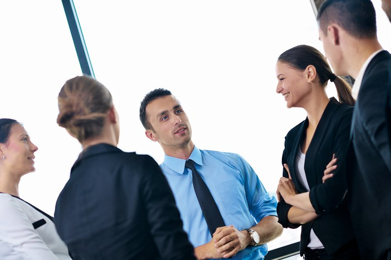 Gruppe von Angestellten steht im Kreis und unterhält sich.